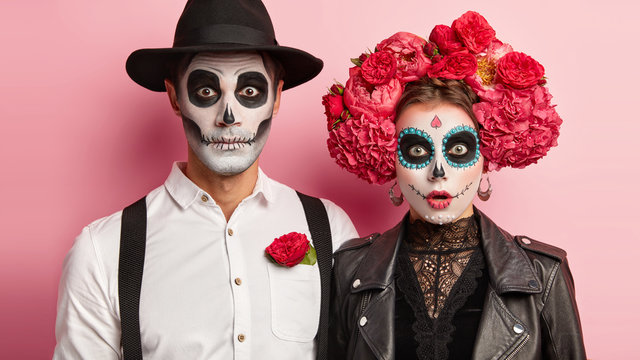 Surprised zombie man and spooky female wear mexican makeup, celebrate day of dead, wear black hat, white shirt traditional flower wreath ready to go on cemetery gather to pray and remember dead people