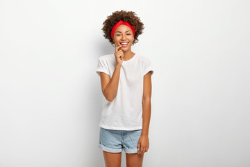 Studio shot of lovely curly haired woman enjoys pleasant moment, smiles gently, wears red headband, casual t shirt and denim shorts, laughs as has good sense of humor, isolated on white background