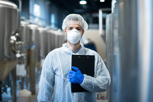 Technologist with protective mask and hairnet standing at factory production line. Food or beverage processing factory.