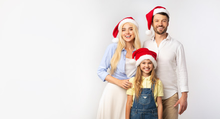 Family Of Three In Christmas Santa Hats Standing In Studio