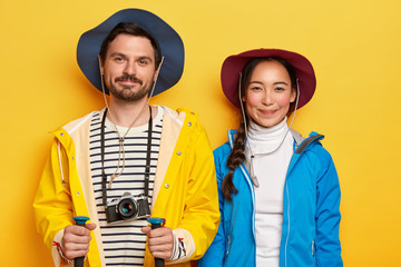 Diverse couple have hiking trip, dressed casually, pose with trekking sticks, retro camera, cover long distance on foot, pleased by memorable travel, breath fresh air and enjoy nature. People and rest
