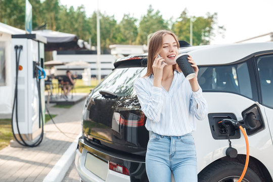 Young adult woman drinking coffee, charging electric car, talking on smartphone