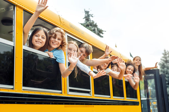 Classmates going to school by bus leaning out of the window waving to camera smiling positive