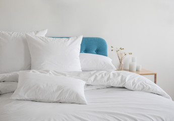 White pillows and duvet on the blue bed. White pillows, duvet and duvet case on a blue bed. White bed linen on a blue sofa. Bedroom with bed and beddin.Front view