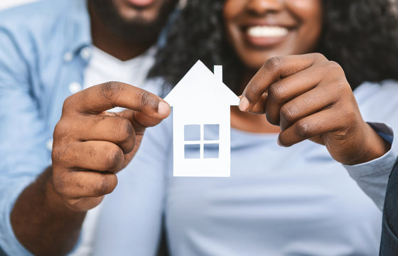 Close up of african couple holding wooden house