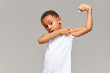 Look at my bicep. Picture of funny Afro American in casual white t-shirt posing isolated at gray studio wall pulling up sleeve, showing his tensed arm muscle. Childhood, fitness and sports concept