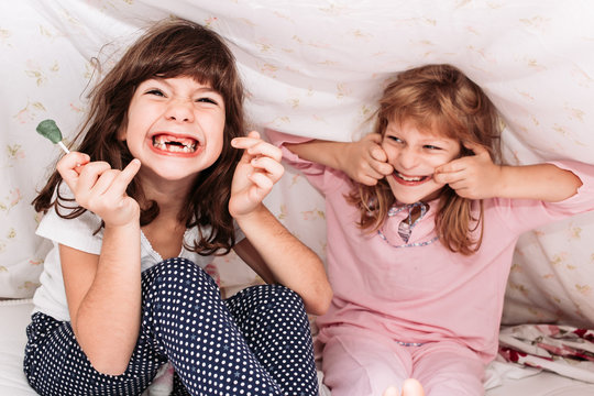 Close-up photo of little girls eating candy. Dental problems, teeth protection.
