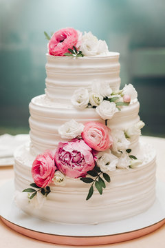 Appetizing big fresh pastry cake covered by white cream icing and decorate sweet flower serving on table. Tasty wedding event delightful dessert ready for banquet at blue light illuminate background