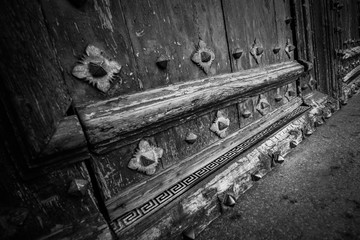 Black and White of an Ancient and worn door with elaborate ornaments
