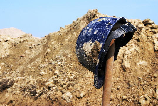 Blue safety hard hat on top of a spade at an archaeological excavation. Pile of dirt and stroke of blue sky in the background