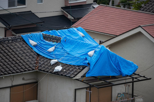 Tattered blue tarp on roof after strong typhoon wind damage