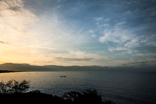 Sunrise over Lake Tanganyika with silhouettes of several traditional fishing boats. Tanzanian mountains in the background