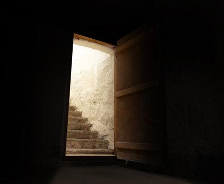 Open door in spooky dark basement with brightly lit stairs