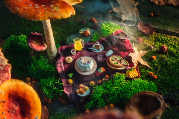 Picnic under toadstool mushroom, miniature food in the forest, tiny world concept. Magical art photo header.