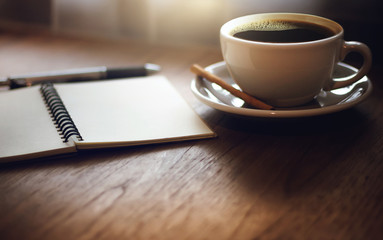 Closeup black coffee in cup with open blank notebook on wooden table. Vintage light and dark tone