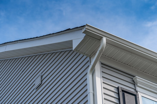 Gable with gray horizontal vinyl siding, white frame gutter guard system, fascia, drip edge, soffit, on a pitched roof attic at a luxury American single family home neighborhood USA