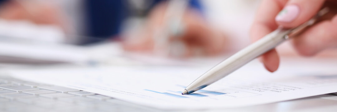 Female hand point silver pen to graph on seminar. Bank credit loan money invest tax situation review income calculation form white collar train investment audit board members session concept