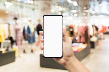 Mockup mobile phone image of woman hand holding smart phone with blank white screen for your advertisement on blurred abstract background of women clothing fashion shop.