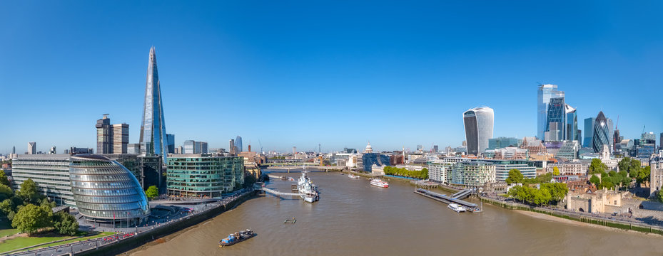 Aerial cityscape panorama of the Thames river on a sunny day with the City Hall, Shard skyscraper and London City Financial district skyline.
