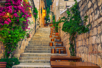 Foto op Plexiglas Smal steegje Narrow street and street cafe decorated with flowers, Hvar, Croatia