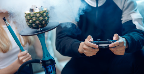 Man holds gamepad in hands, in background smoke from hookah