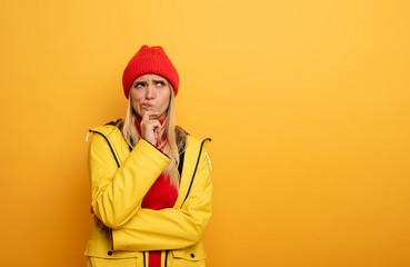 Girl thinks about something. Confused and pensive expression. Yellow background