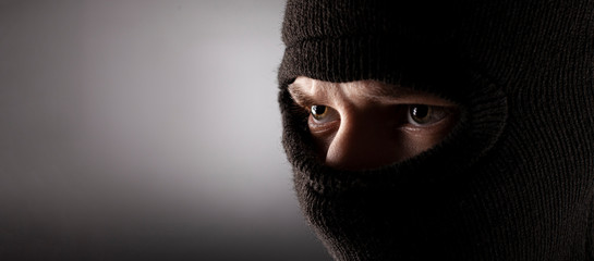 angry man in a balaclava on a dark background. - fototapety na wymiar