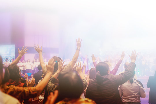 Soft focus of Christian worship with raised hand,m