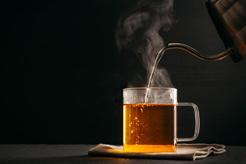 Foto op Plexiglas Thee The process of brewing tea, pouring hot water from the kettle into the Cup, steam coming out of the mug, water droplets on the glass, black background