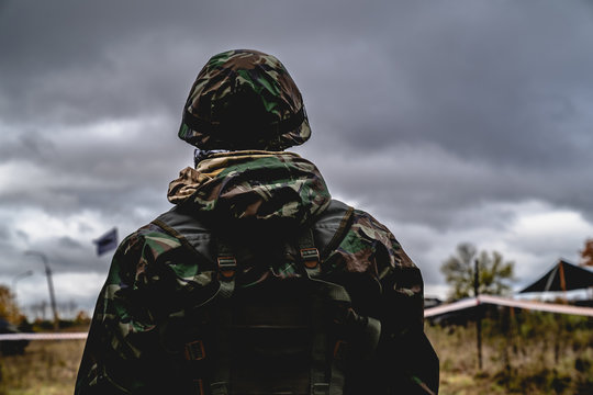 Soldier in the uniform and helmet at the battle field looking forward. Cloudy sky at the background. Back view