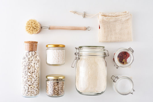 Glass jars with food ingredients on a white background, top view. Zero waste concept. Kitchen background with eco friendly utensils