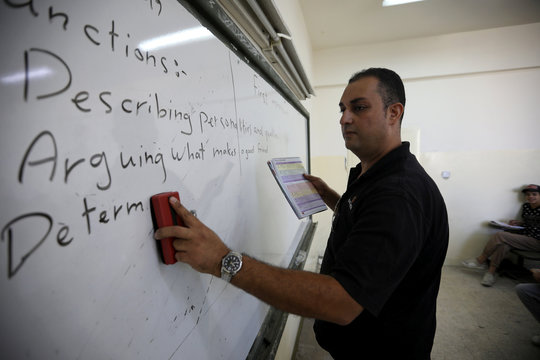 A teacher writes on a white board at one of the public schools during the first day after the end of teachers' one-month strike in Amman