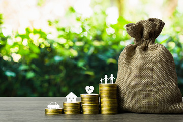 Savings money for the future concepts. Family member, car, house, healthy on stack of coins with money bag on wood table. Depicts saving for wealth and life. fundraising concept. Fototapete