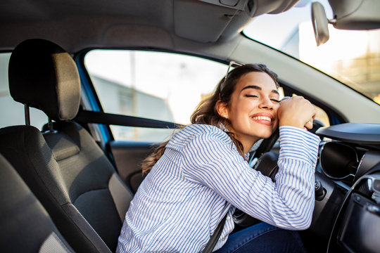 Young Woman Embracing Her New Car. Excited young woman and her new car indoors. Young and cheerful woman enjoying new car hugging steering wheel sitting inside