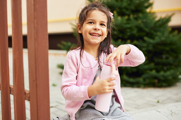 Cute little girl smiling and opening her eco glass bottle for drinking a water, sitting outdoors. Happy child pupil relaxing outside after preschool lessons. People, education concept