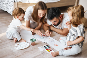 young parents studing with children , developing their painting skills, close up photo