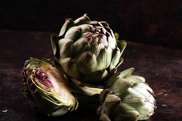 artichokes on rustic dark background. fresh organic artichoke flower.