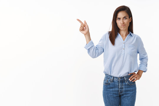 Disappointed angry serious-looking caucasian woman with tattooed arm, smirk impatient, pointing left pouting perplexed, scolding daughter, indicate sideways copyspace, stand white background