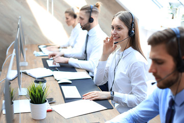 Female customer support operator with headset and smiling accompanied by her team.