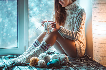 Cozy woman in knitted winter socks and white warm sweater enjoys knitting on a window sill on checkered plaid on the window at home in winter time