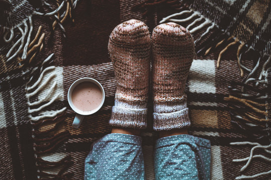 Cozy woman in knitted winter warm socks and in pajamas resting on checkered plaid blanket with a cup of hot cocoa at home in winter time. Cozy time and winter drinks. Top view