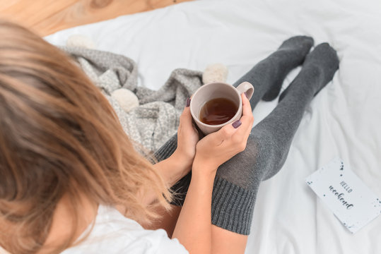 Woman`s legs in leg warmers in bed. Beautiful girl sitting in her bed and drinking morning tea