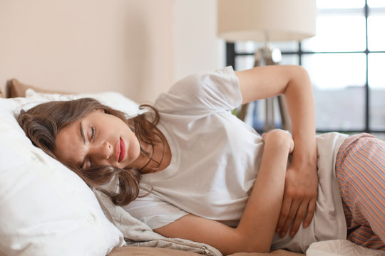 Sick woman on bed concept of stomachache.