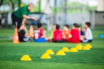 Selective focus to yellow cone markers are soccer training equipment on green artificial turf with blurry kid players training background. Material for training class of football academy.