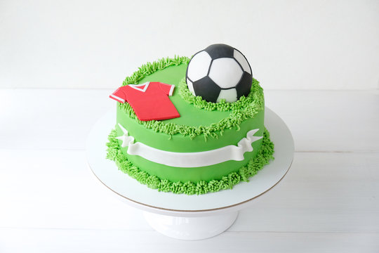 Cake on a football theme decorated with green grass and soccer ball on white background.