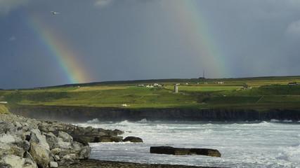 Irland mit dunklen Himmel und Regenbogen mit Gischt