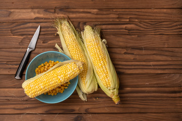 corn on woody table with knife and blue plate