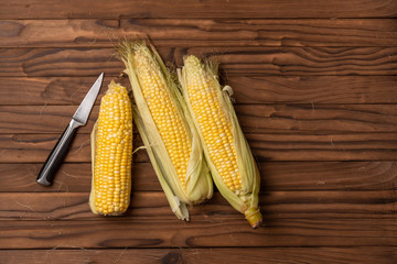 corn on woody table with knife