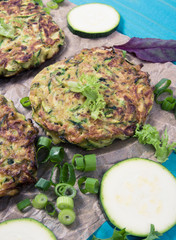 Zucchini pancakes with chives on a wooden table.