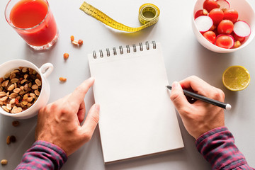 man writes calories to notepad concept diet